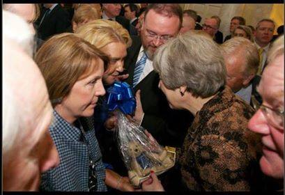 Councillor Dianne Beagrie with MP David Duguid handing over the handmade Peterhead bear to Theresa May