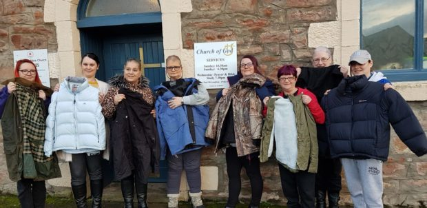Members of Serenity pictured with the donated jackets, some of which have been distributed to the city's homeless.
