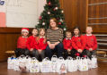 Pupils from Mosstodloch Primary with their food bags and Gillian Pirie from Moray Foodbank