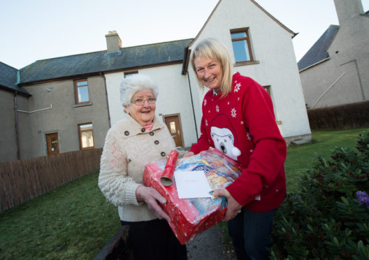 Pictures show Land lady, Lynn Mitchell of The Brander Arms in Lossiemouth with her food parcels and delivering the parcels to an older lady in Lossiemouth. In the bar you can see all of the donation envelopes.  Picture: Lyn Mitchell (right) and (left) Helen Donaldson.