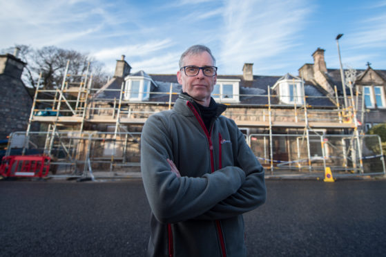 Phillip Murray on Rothes High Street in Rothes, Moray with his parents house covered in Scaffolding behind him.