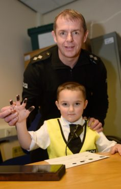 Picture by SANDY McCOOK  Reporting for duty.........Brax Walker (5) of Garmouth at Elgin Police Station on Saturday afternoon.   Also in the photograph is Inspector Neil Campbell of Police Scotland.