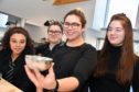 Technician Megan Falconer showing Banff pupils (L ro R) Ayesha Argo, Claire Campbell and Alana Cameron a hammered silver bowl at the Smiddy