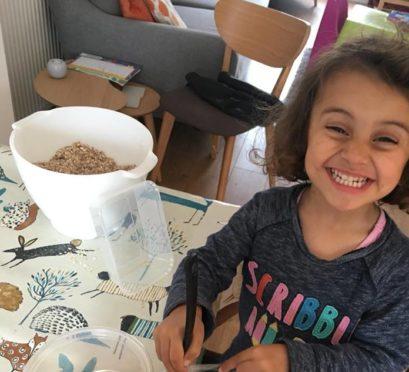 Priya, 3, assembling packets of reindeer food.