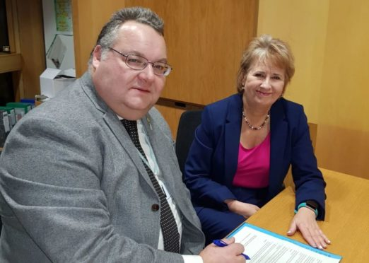 Moray Council leader Graham Leadbitter signs the charter with the Scottish Government's environment and climate change minister Roseanna Cunningham.