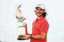 Tommy Fleetwood celebrates with the Abu Dhabi HSBC Golf Championship trophy