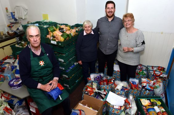 Angus Hay, Mary Kitchen, pastor Rob McArthur and Wendy Boothroyd show off the food donations.