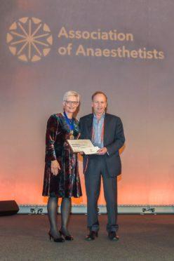 Dr Paul Upton receiving his award from Dr Kathleen Ferguson.