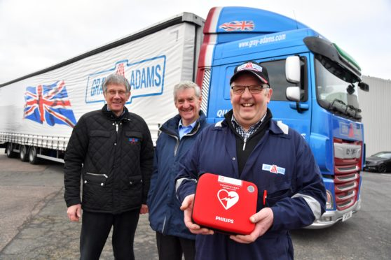 Murray Littlejohn of Gray and Adams shows one of the defibrillators which is being supplied to the company's tractor units watched by joint managing director James Gray (L) and MSP Peter Chapman