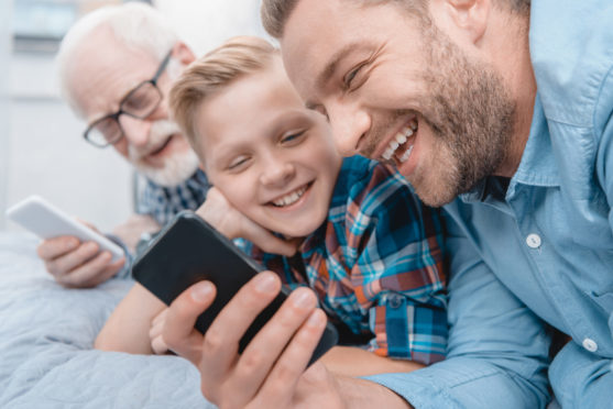Little boy, his father and grandfather lying on bed with smartphones