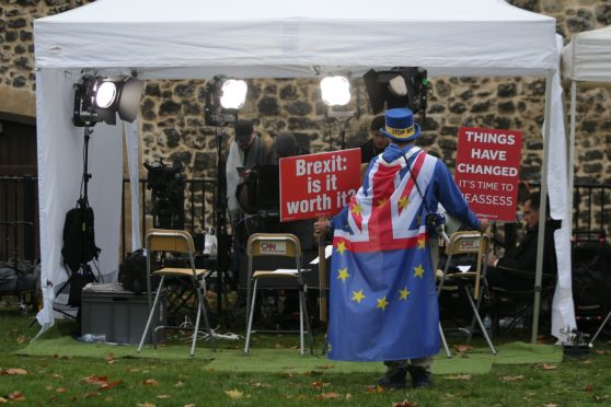 Anti-Brexit campaigner Steve Bray stands with placards with anti-Brexit slogans near the mobile studios of media broadcasters on College Green near the Houses of Parliament in London on November 16, 2018. - British Prime Minister Theresa May battled on November 16 to salvage a draft Brexit deal and her own political future. After a tumultuous Thursday in which ministers resigned and members of her own party plotted to oust her, May  faced the public to defend her position, in a radio phone-in. (Photo by Daniel LEAL-OLIVAS / AFP)        (Photo credit should read DANIEL LEAL-OLIVAS/AFP/Getty Images)