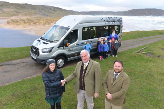 Katherine Wood of Farr High School receives new school bus from Tim Kirkwood and Andrew Adamson of Wildland Ltd
