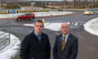 MP Douglas Ross and Councillor Marc Macrae at the roundabout junction of the A98 A96 and Fochabers Village entrance.