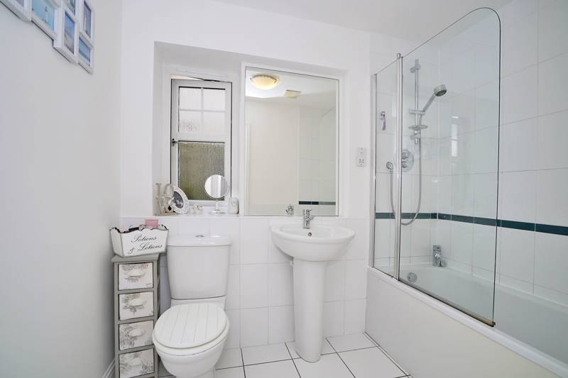 Bathroom: Fitted with a white three-piece suite, complete with an overbath mixer shower and shower screen