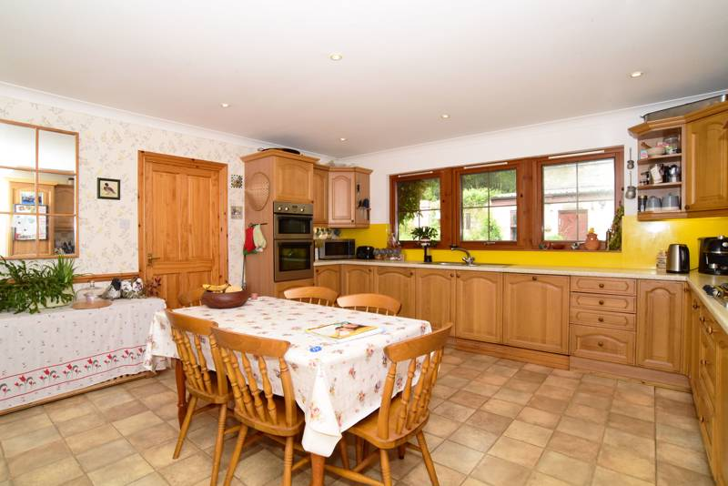 Kitchen: Has a range of wall and floor storage units, space for table and chairs and a door leading through to a utility room