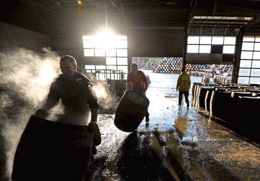 Coopers work on whisky casks at the Speyside Cooperage in Craigellachie.