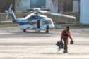 A pilot walks in front of a Bristow offshore helicopter at their base at Aberdeen Airport