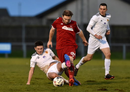 Dane Ballard (red) in action for Deveronvale against Rothes in the Highland League  The Press & Journal Scottish Highland League. Deveronvale (red) v Rothes (white) at Princess Royal Park, Banff. Picture of Stephen Rennie (white) sliding in on Dane Ballard (red).