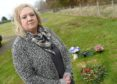 Lynda Fraser at the grave of her husband Stuart in Auldearn Cemetry, where a precious heart shaped wreath was removed by staff while tidying the graveyard of Christmas wreaths.