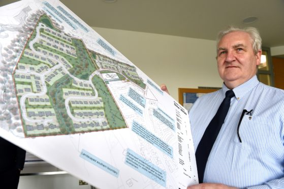 Architect Sam Sweeney holds aloft plans after a public consultation was held yesterday over a potential housing development at Old Edinburgh Road South, Inverness.