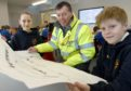Ian MacDonald, Special Works Manager with contractors Morgan Sindal with pupils Martha Macintosh and Angus Smith both of Primary 7.