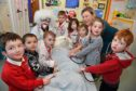 DR POTTY, MSP GILLIAN MARTIN AND THE DINKY DOCTORS OF MINTLAW PRIMARY NURSERY CLASS CHECK THE TEDDY FOR SIGNS OF LIFE.
