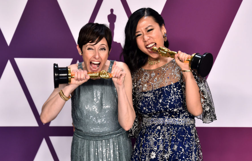 Becky Neiman-Cobb (left) and Domee She with the award for Best Animated Short Film for Bao.