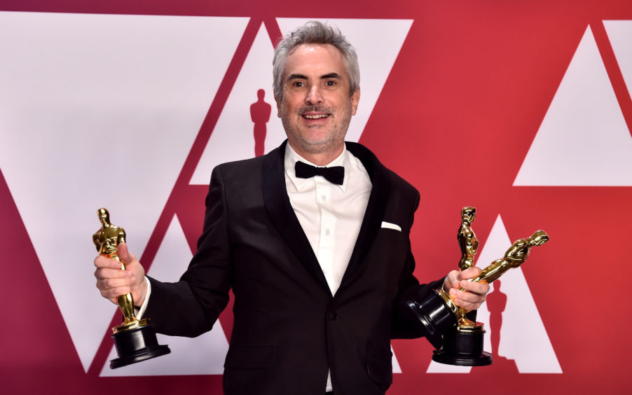 Alfonso Cuaron with his Best Director, Best Foreign Film and Best Cinematography awards.