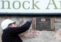 A workmen installs the plaque at the Kilmarnock Arms Hotel