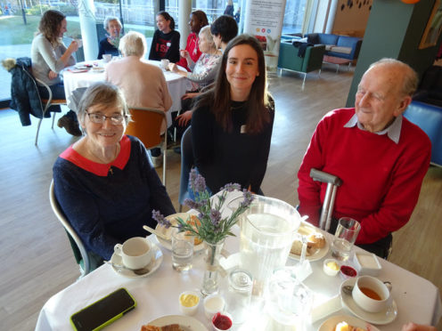 Student Jenna Scott with Contact the Elderly guests at a tea party hosted by the International School of Aberdeen