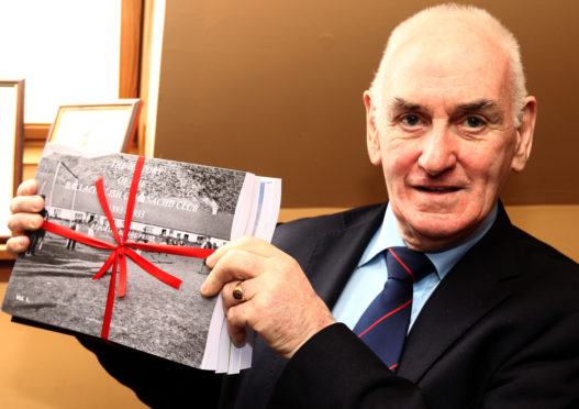 Ian MacPhee with the book he compiled telling the extensive 125 year history of Ballachulish Shinty Club. Picture by Kevin McGlynn