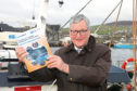 Ken Amer - Fergus Ewing brandishing the Future of Fisheries Management in Scotland paper at Kirkwall Harbour, Orkney