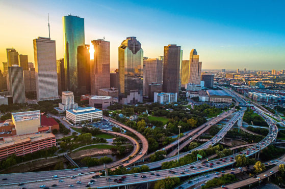 Houston - istock - Houston Texas aerial drone sunrise view cityscape skyline colorful morning downtown  - highways , traffic , office buildings and high rises Home sales and modern architecture of the Houston real estate market - new modern homes for sale on Houston Texas on a sunny day