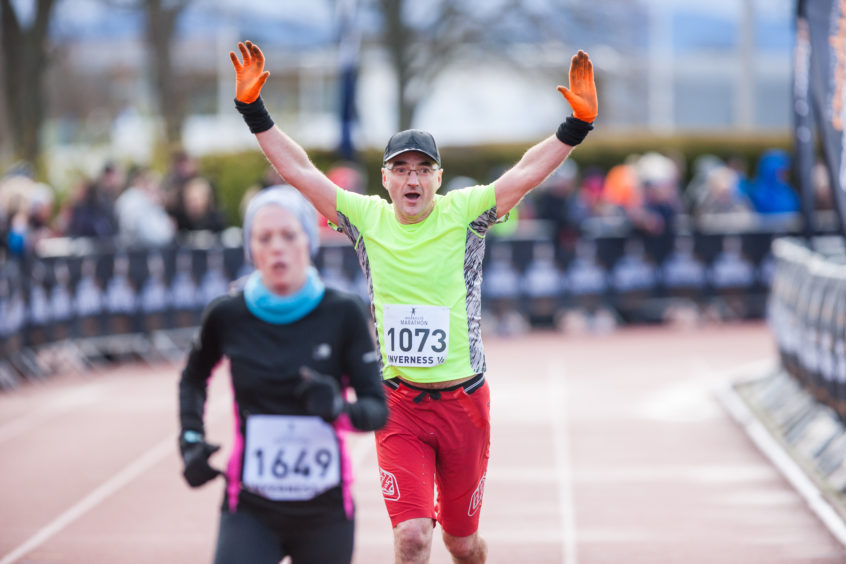 A runner celebrates as he crosses the line at the Inverness 1/2 Marathon.