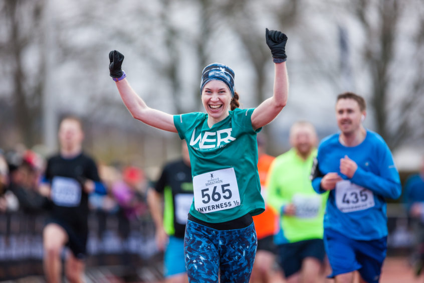 A runner celebrates as she crosses the line at the Inverness 1/2 Marathon.