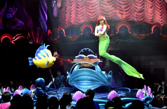 """Disney's Little Mermaid character Ariel sings and displays wire-action performance in the air during the press preview of the new attraction """"King Triton's Concert"""" at the Tokyo DisneySea in Urayasu, suburban Tokyo on April 20, 2015. The new musical show will open for public from April 24. Disney theme park Tokyo Disneyland and Tokyo DisneySea marked record high visitors of 31.38 million in the fiscal 2014 year ended March.   AFP PHOTO / Yoshikazu TSUNO        (Photo credit should read YOSHIKAZU TSUNO/AFP/Getty Images)"""