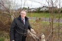 Councillor Duncan Macpherson with some of the damaged trees in Castlehill Community Woodland, Cradlehall, Inverness.