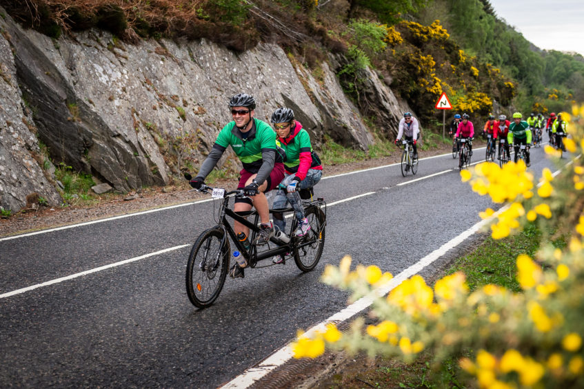 A pair of Macmillan Cancer Support cyclists riding a tandem bike as part of the Etape Loch Ness.