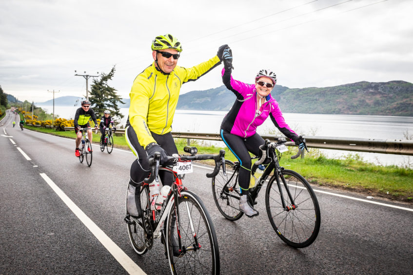 Cyclists making their way along the A82 with Loch Ness in the background.