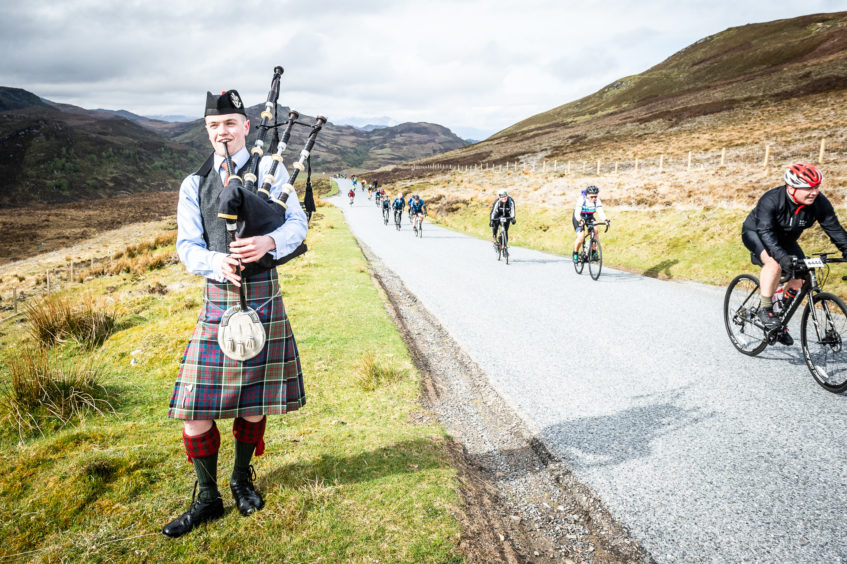 A lone piper waits to pipe the riders home at the top of the Suidhe viewpoint and the end of the King of the Mountain stage.