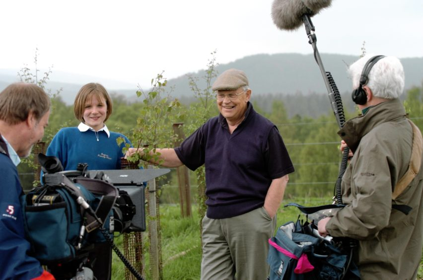 Presenter Jim McColl with Finzean primary pupil Lauren Duncan being filmed by the BBC crew.
