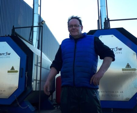 Neil Benzie with the two biomass boilers, the one on the right which has been off since January and the one on the left which was still on at the time of the picture on April 29