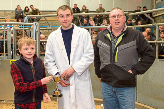 James Gunn, centre, was presented his trophy on behalf of sponsors, Mackay, West Greenland, by 7-year-old Dhail Mackay, whose father, Andrew, looks on.