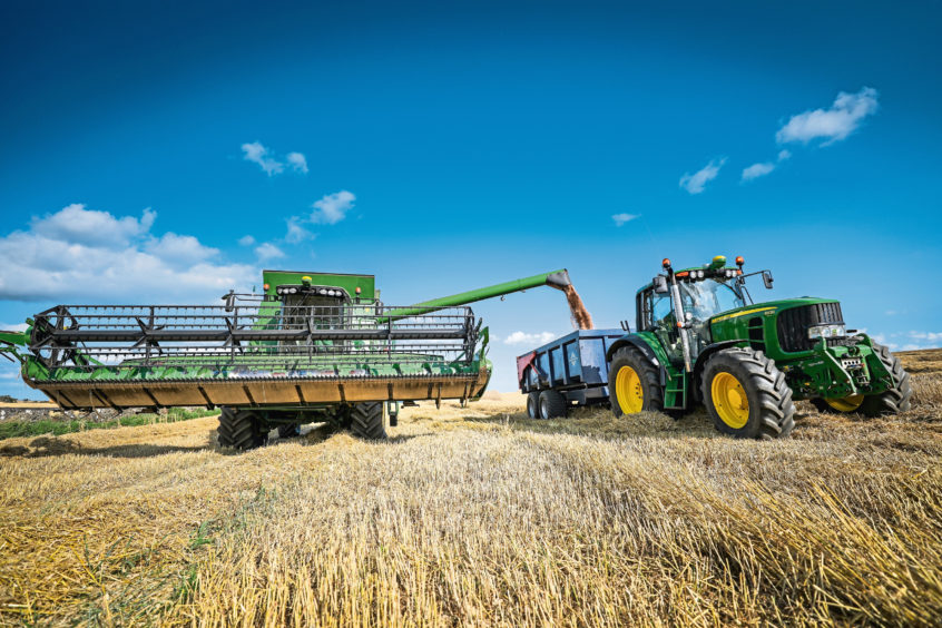 Combine harvester cutting wheat crop on Banchory Farm.