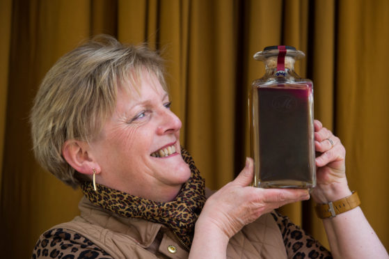 Craigellachie Village Council chairwoman Jane Tweedie with a 1960s bottle of Macallan valued at up to £8,000.