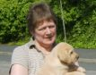 Christine Neish with one of the guide dog puppies she helped prepare for a life of helping others.