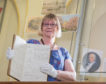 Elgin Museum Janie Mackenzie with the original admissions book for Dr Gray's Hospital from when it opened in 1819.