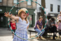 Ottilie Scott hula hooping as part of Elgin business improvement district's Easter day.