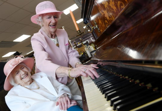 Elsie Walker and Cathie Knox play a rendition of Jesus Loves Me on the piano
