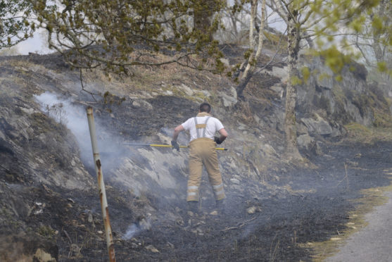 A firefighter works on keeping the flames from breaking out again in the fire ravaged glens between Lochailort and Morar.